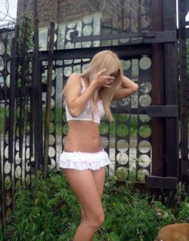 A girlfriend walks around the yard in a short skirt